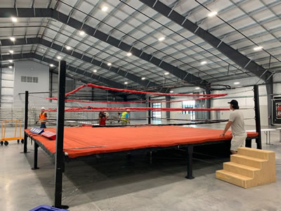 Boxing ring adjustments in preparation for event